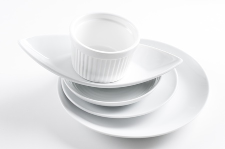A stack of clean white different dishes on a white background photo