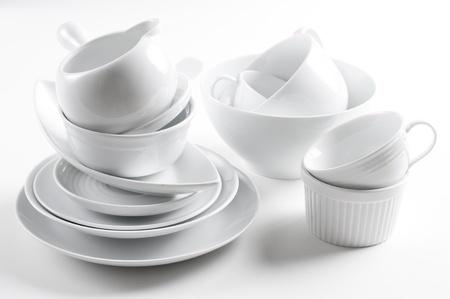Veel witte servies en keukengerei op een witte achtergrond