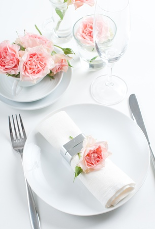 Holiday romantic table setting with pink roses on a white background photo