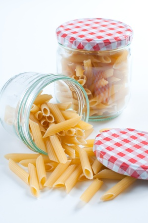 scattered: Two jars with checkered caps with the Italian raw pasta Stock Photo