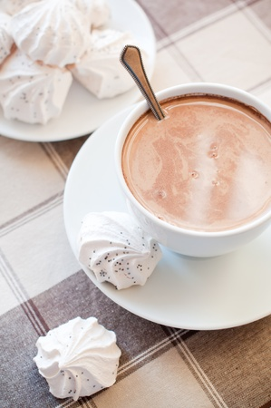 hot coffees: A cup of coffee and meringues on brown cloth