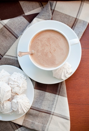hot coffees: A cup of coffee and meringues with a brown cloth on a wooden table