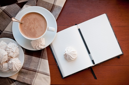hot coffees: A cup of coffee, meringues, and a notepad on a desk Stock Photo