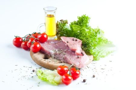 carnes: La carne fresca cruda, tomate y una ensalada en el fondo blanco Foto de archivo