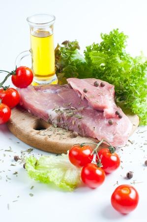 carnes y verduras: La carne fresca cruda, tomate y una ensalada en el fondo blanco Foto de archivo