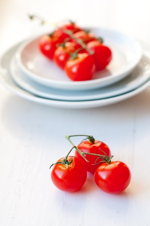 Ripe cherry tomatoes and a plates on a white background photo