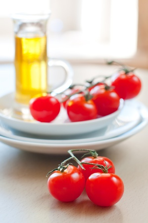 Summer ripe cherry tomatoes and plates on the table photo
