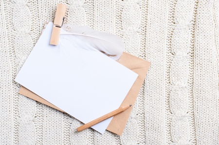 Empty cardboard card and envelope on texture of knitted sweater photo