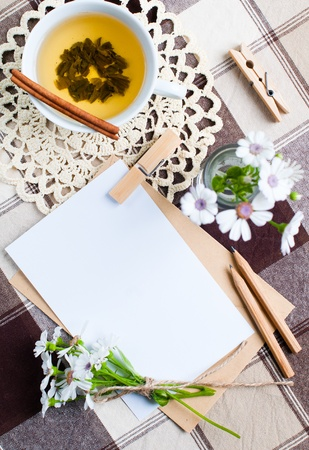 composition of the empty cardboard card with flowers and an envelope on fabric photo