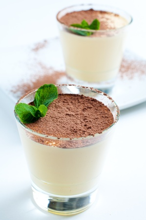 Two creamy vanilla desserts with cocoa and mint leaf Stock Photo