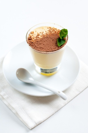 Creamy vanilla dessert with cocoa and mint leaf photo
