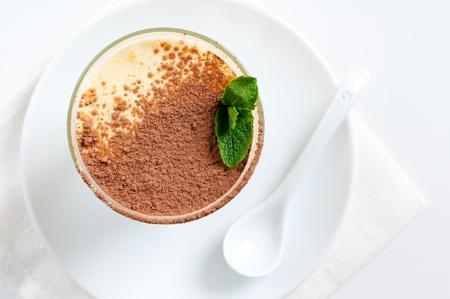 Creamy vanilla dessert with cocoa and mint leaf photo