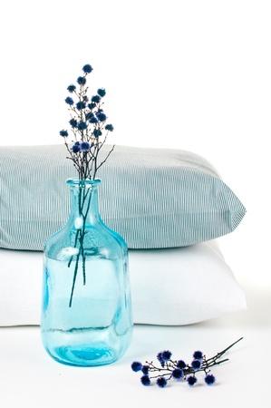 Kussens en een blauwe vintage fles op een witte achtergrond