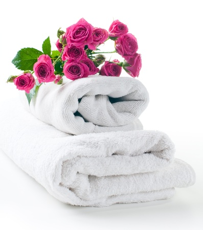 towels luxury: Two clean white terry towels and a bouquet of roses on a white background