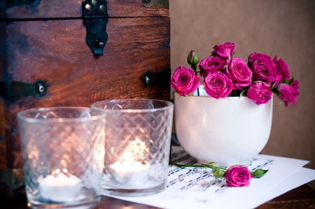 bouquet of roses in a cup, candles, notes and a wooden chest in a retro style photo