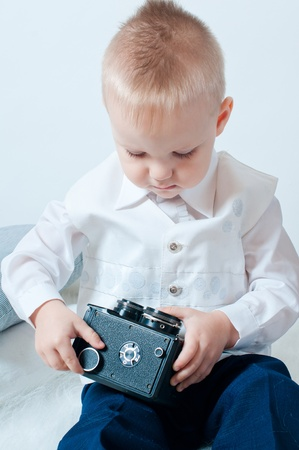 A little boy plays with an old camera in studio Stock Photo - 12780752
