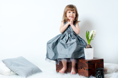 Smiling little girl in a beautiful dress sitting in the studio photo