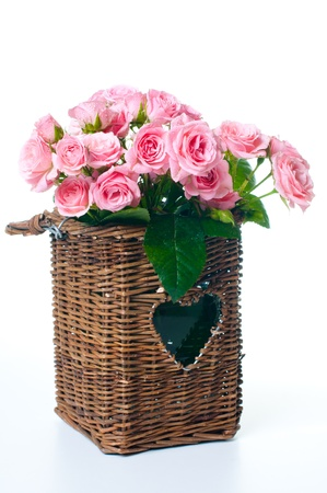 bouquet of pink roses in a wicker basket on a white background photo