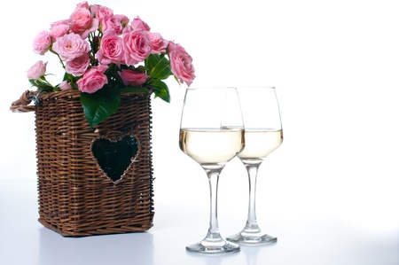 Two glasses of white wine and a bouquet of pink roses in a wicker basket photo