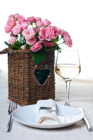 A glass of white wine and a basket of roses on the table photo