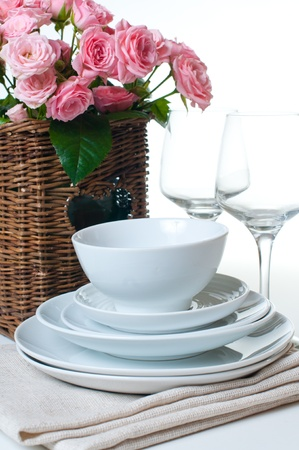 china rose: Clean dishes, towels and a basket of flowers on a white background