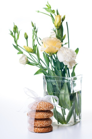 Bouquet of Yellow Eustomas and delicious biscuits on a white background photo