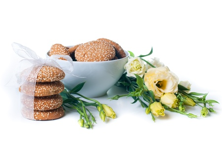 delicious cookies and a bouquet of yellow Eustomas on a white background photo