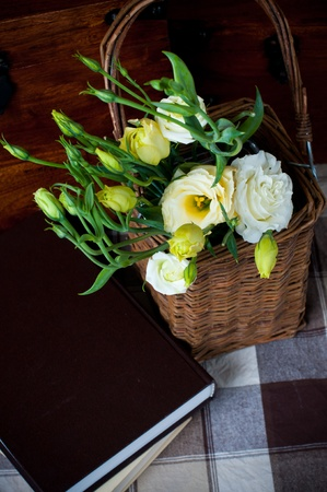 colorful still life: Close-up of a bouquet of yellow flowers in a wicker basket, books and wooden chest Stock Photo