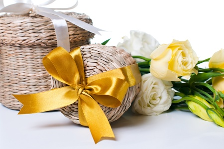 Two wicker gift box with a yellow ribbon and a bouquet of eustomas on a white background photo