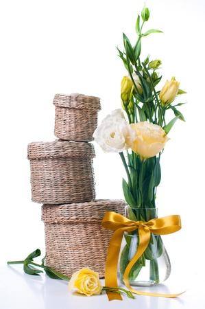 Drie rieten dozen en een bos van gele bloemen op een witte achtergrond Stockfoto