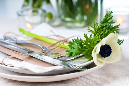 anemone flower: Closeup of holiday table setting with white flowers and candles Stock Photo