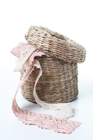 Wicker box with lace ribbons on a white background photo