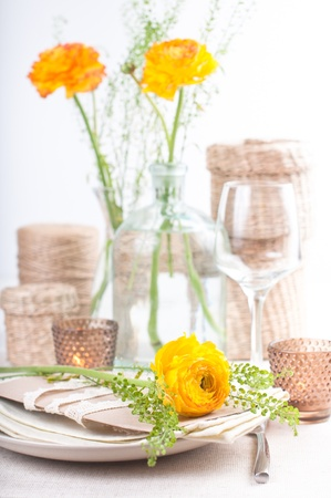 wedding table setting: festive dining table setting with yellow-orange flowers ranunkulus