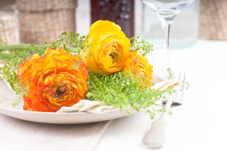 festive dining table setting with yellow-orange flowers ranunkulus photo