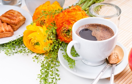 Elegant fresh breakfast: coffee, fruit, pastries, and flowers on a white background photo