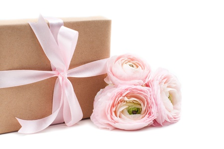 gift tied with ribbon and pink flowers on a white background photo