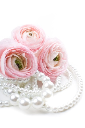Close up of pink flowers and pearl beads on a white background photo