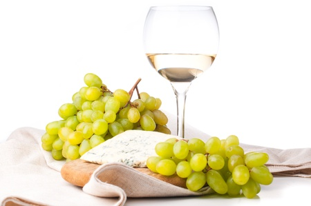 glass of white wine, blue cheese and a bunch of white grapes on white background photo
