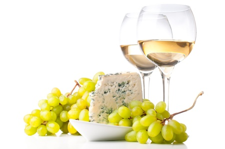 Two glasses of white wine, blue cheese and a bunch of white grapes on white background photo