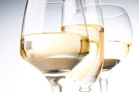 Tre bicchieri diversi di vino bianco, primo piano