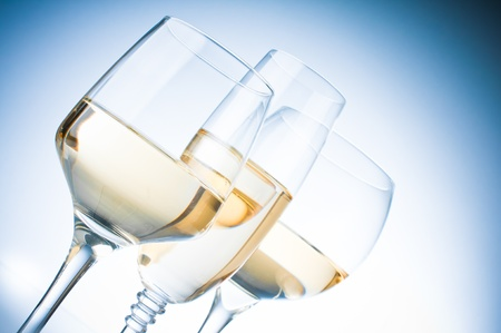 Three different glasses of white wine on a blue background, close-up photo