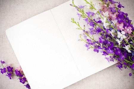 Open kladblok en een boeket van paarse wilde bloemen close-up