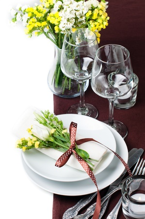 Festive table setting and decoration with fresh flowers in brown and yellow photo