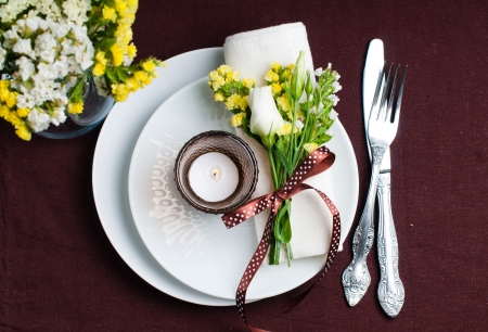 restaurant setting: Festive table setting and decoration with fresh flowers in brown and yellow