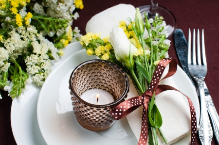 Festive table setting and decoration with fresh flowers in brown and yellow