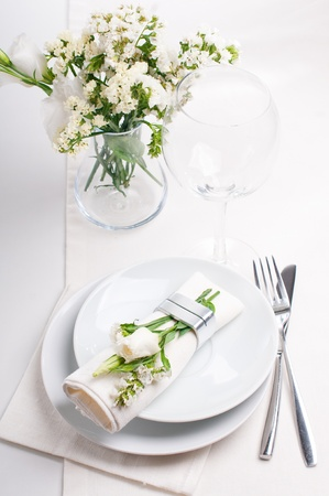 plate setting: Festive table setting and decoration with fresh flowers in white colors Stock Photo
