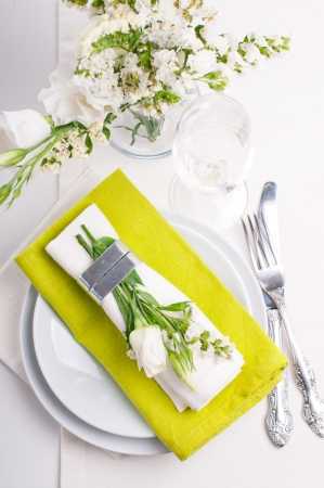 Festive table setting and decoration with fresh flowers in green photo