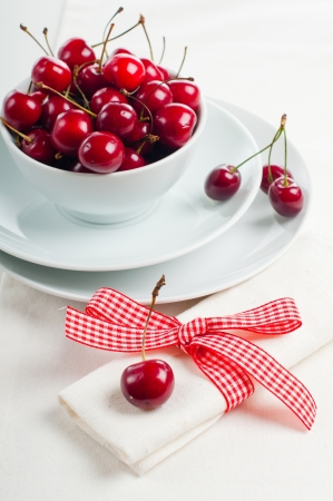 Festive table setting and decoration with fresh flowers and sweet cherry photo