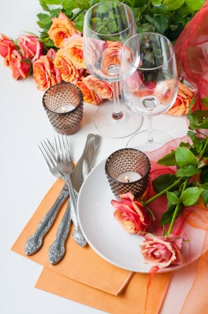 to place: Festive table setting with roses and candles in shades of orange on a white background Stock Photo