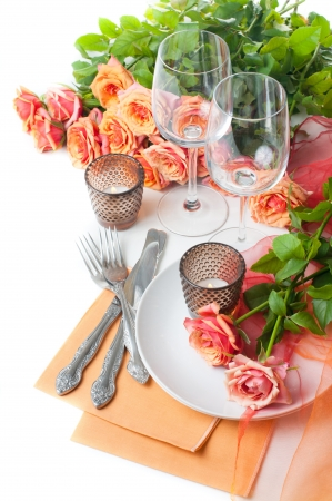 receptions: Festive table setting with roses and candles in shades of orange on a white background Stock Photo